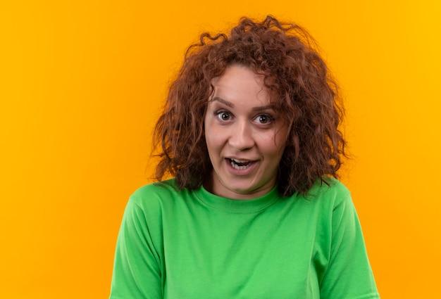 Jonge vrouw die met kort krullend haar in groene t-shirt verraste status kijkt