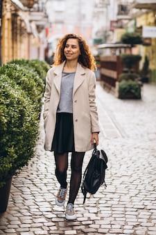 Jonge vrouw die met krullend haar bij een koffiestraat loopt