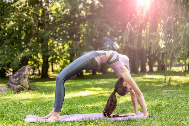 Jonge vrouw die met lang haar gymnastiek- oefening uitvoert