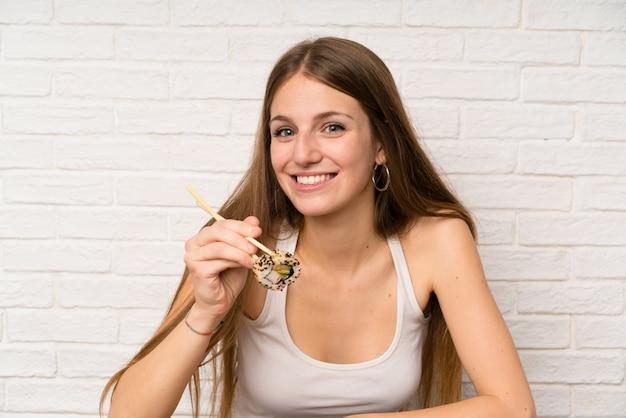 Jonge vrouw die met lang haar sushi eet