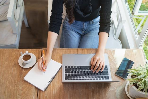 Jonge vrouw die met laptop aan de houten lijst thuis werkt