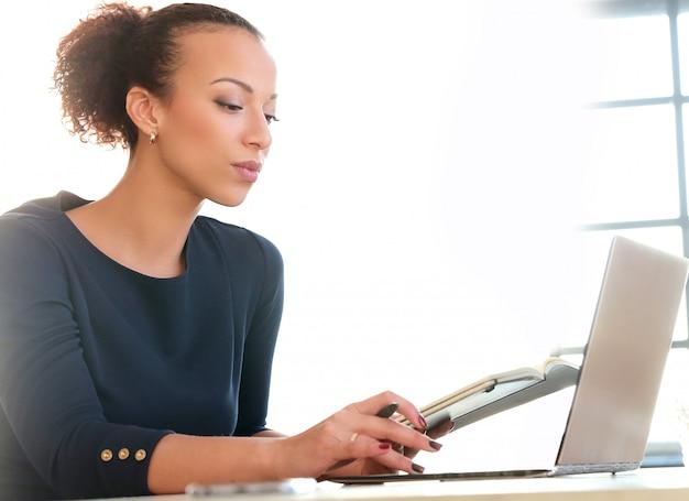 Jonge vrouw die met laptop en agenda werkt