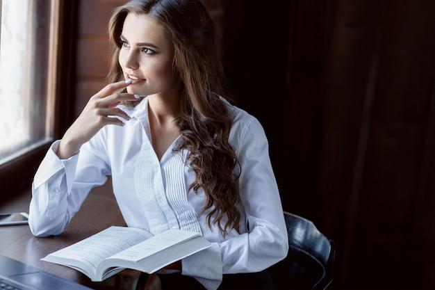 Jonge vrouw die met laptop en documenten werkt. mooi vrouwelijk leesboek dichtbij venster.