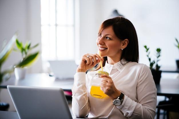 Jonge vrouw die met laptop en het drinken jus d'orange werkt