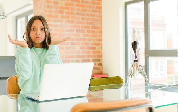 Jonge vrouw die met laptop werkt