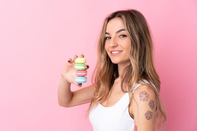 Jonge vrouw die met macarons over geïsoleerde roze muur veel glimlacht