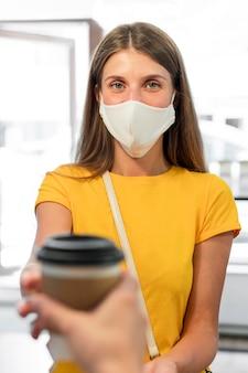Jonge vrouw die met masker koffie koopt