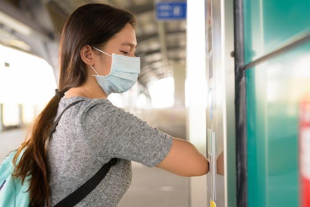 Jonge vrouw die met masker op liftknop met elleboog drukt om verspreiding van het coronavirus op skytrain-station te voorkomen