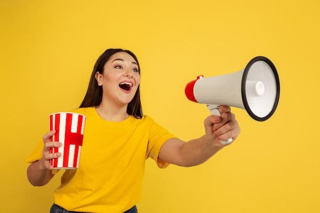 Jonge vrouw die met megafoon roept en popcorn houdt