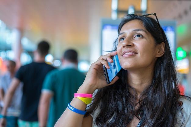 Jonge vrouw die met mobiele telefoon spreekt