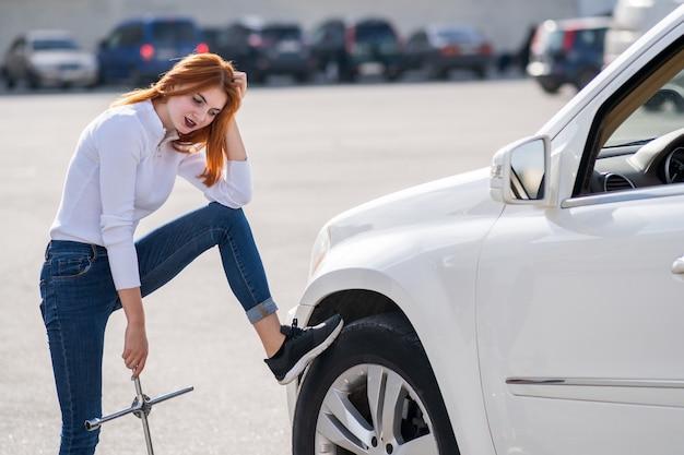 Jonge vrouw die met moersleutel op hulp wacht om wiel op een gebroken auto te veranderen.