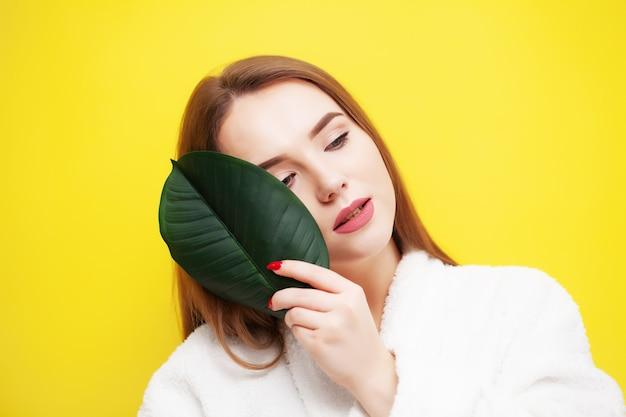 Jonge vrouw die met mooie huid een groen blad houdt dichtbij haar gezicht