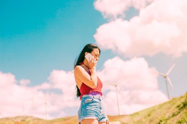 Jonge vrouw die met nadenkende blik telefoneert