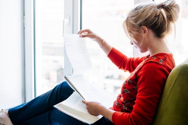 Jonge vrouw die met notitieboekje bestudeert