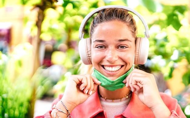 Jonge vrouw die met open gezichtsmasker en hoofdtelefoons glimlacht