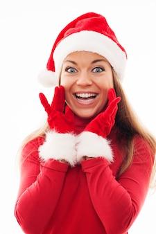 Jonge vrouw die met santahoed en handschoenen opgewekt kijkt