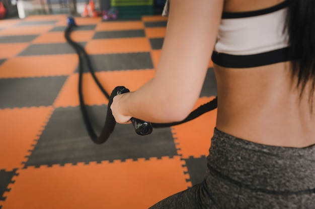 Jonge vrouw die met slagkabels uitwerken in de gymnastiek.