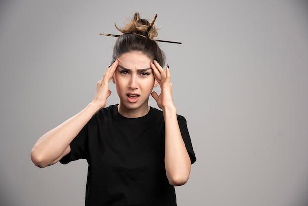 Jonge vrouw die met slordig broodje haar hoofd op grijze muur houdt.