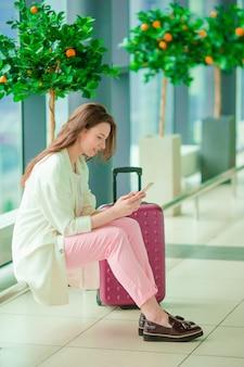 Jonge vrouw die met smartphone in internationale luchthaven op vlucht wacht