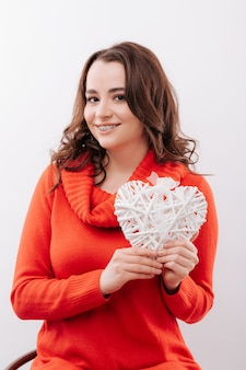 Jonge vrouw die met steunen een hart houdt