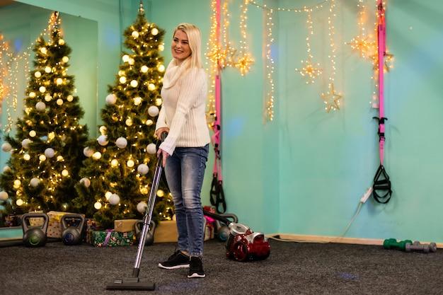 Jonge vrouw die met stofzuigervloer schoonmaakt na nieuwjaarsnaalden van kerstboom in hal