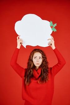 Jonge vrouw die met tekstballon omhoog kijkt