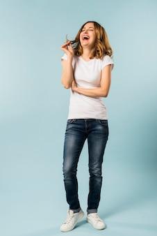 Jonge vrouw die met vreugde tegen blauwe achtergrond lacht