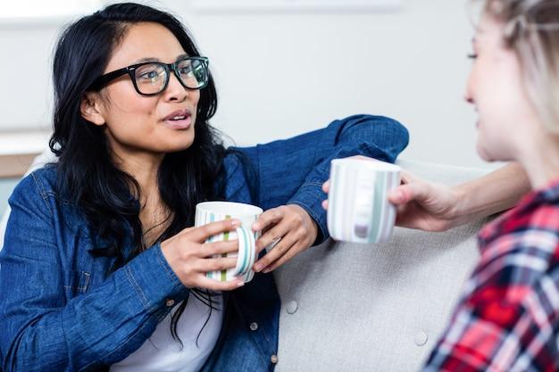Jonge vrouw die met vrouwelijke vriend spreekt terwijl het drinken van koffie