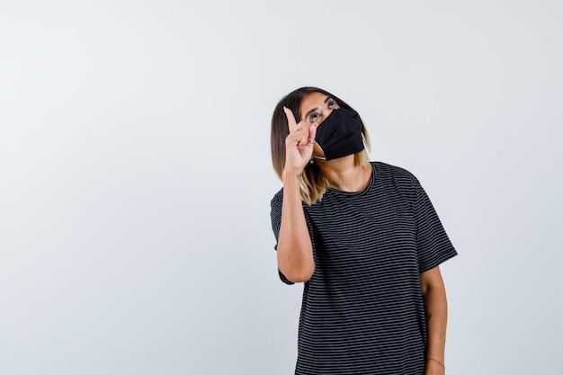 Jonge vrouw die met wijsvinger benadrukt, omhoog kijkt in zwarte jurk, zwart masker en peinzend, vooraanzicht kijkt.