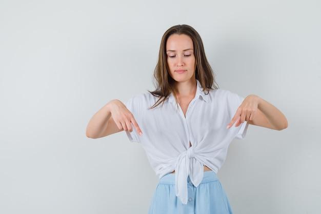 Jonge vrouw die met wijsvingers in witte blouse en lichtblauwe rok naar beneden wijst en ernstig kijkt