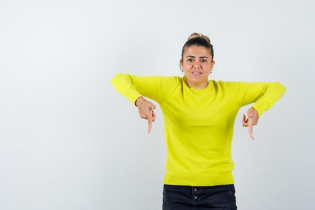 Jonge vrouw die met wijsvingers naar beneden wijst in gele trui en zwarte broek en er gehaast uitziet