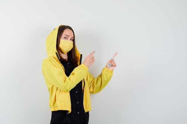Jonge vrouw die met wijsvingers naar rechts wijst
