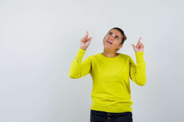 Jonge vrouw die met wijsvingers omhoog wijst in gele trui en zwarte broek en er gefocust uitziet