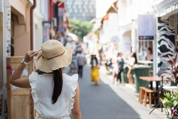 Jonge vrouw die met witte kleding en hoed reist