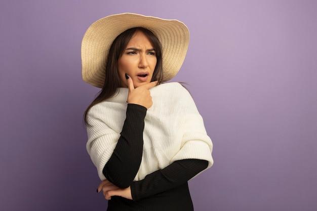 Jonge vrouw die met witte sjaal en de zomerhoed verward en ontevreden opzij kijkt