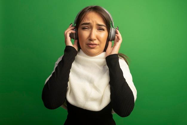 Jonge vrouw die met witte sjaal en hoofdtelefoons verward kijkt