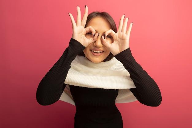 Jonge vrouw die met witte sjaal met gelukkig gezicht glimlacht dat ok teken zoals verrekijker toont die door vingers kijkt