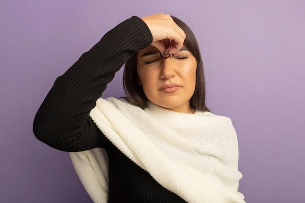 Jonge vrouw die met witte sjaal moe en verveeld kijkt wat betreft haar neus tussen gesloten ogen