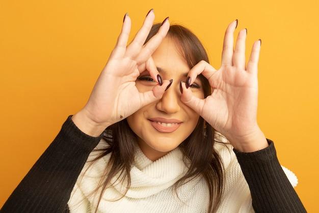 Jonge vrouw die met witte sjaal ok teken als verrekijker gebaar maakt die door vingers vrolijk glimlachen kijken