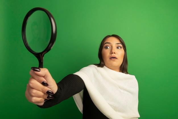 Jonge vrouw die met witte sjaal vergrootglas bekijkt dat wordt verrast