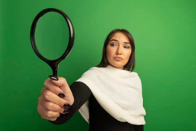 Jonge vrouw die met witte sjaal vergrootglas met ernstig gezicht bekijkt
