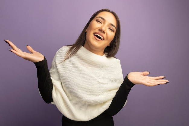 Jonge vrouw die met witte sjaal vrolijk glimlacht spreidt wapens naar de zijkanten