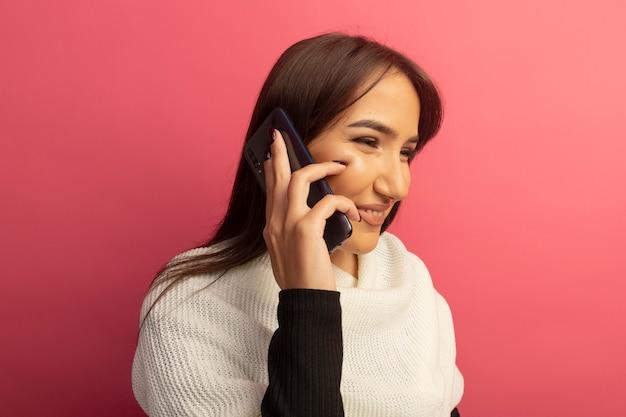 Jonge vrouw die met witte sjaal vrolijk lacht tijdens het gesprek op de mobiele telefoon