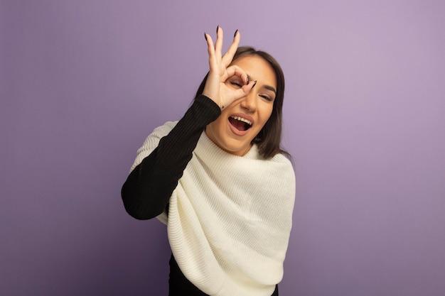 Jonge vrouw die met witte sjaal vrolijk ok teken toont over zijn oog die door teken glimlacht