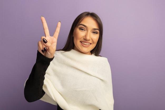 Jonge vrouw die met witte sjaal vrolijk v-teken toont