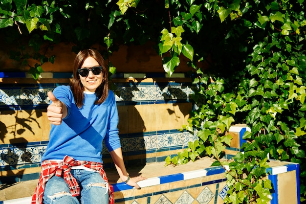 Jonge vrouw die met zonnebril op bank zit