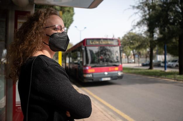 Jonge vrouw die met zwart masker op de bus in de stad wacht