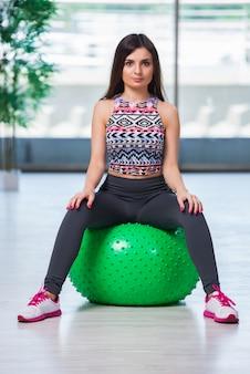 Jonge vrouw die met zwitserse bal in gezondheidsconcept uitoefent