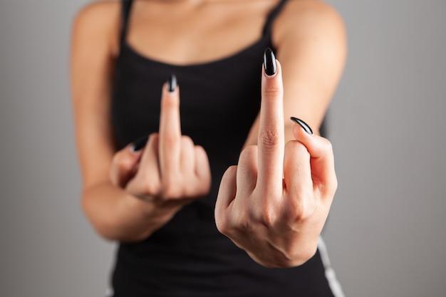 Jonge vrouw die middelvinger laat zien