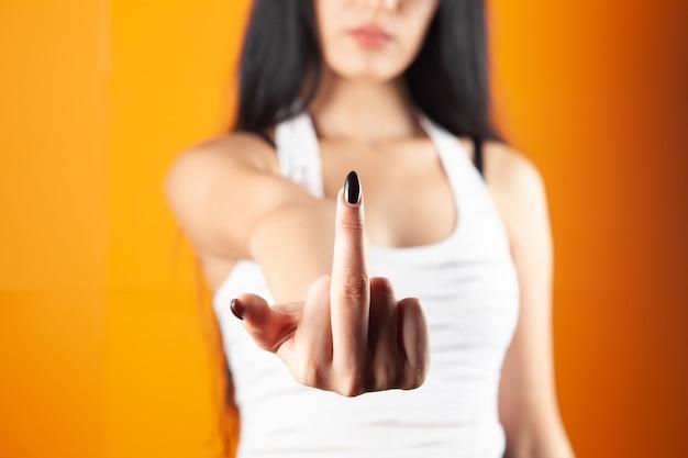 Jonge vrouw die middelvinger op oranje achtergrond toont